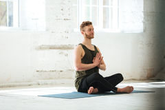 Young smiling guy sitting on a fitness mat and meditating. Young smiling guy with eyes closed sitting on a fitness mat and meditating in the gym Royalty Free Stock Images