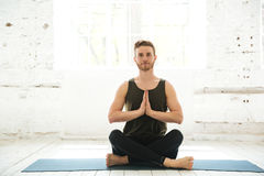 Young smiling guy sitting on a fitness mat and meditating. In the gym Royalty Free Stock Photo