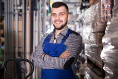 Young smiling guy worker displaying his workplace. At workshop Stock Photo