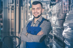 Young smiling guy worker displaying his workplace. At workshop Royalty Free Stock Images