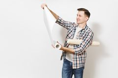 Young smiling handsome man in casual clothes looking on unrolled wallpaper roll isolated on white background. Instruments, tools for renovation apartment room stock photo