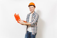 Young smiling handsome man in protective orange hardhat holding opened case with instruments or toolbox isolated on. White background. Instruments for royalty free stock photo