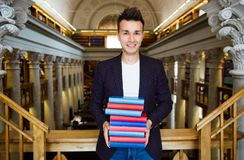 Young handsome man in traditional library. Young smiling handsome man standing in traditional library, holding pile of books. Beautiful interior of old library royalty free stock photos