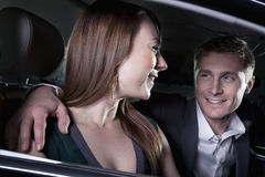 Young smiling, happy, couple sitting in their car and arriving at a red carpet event at night in Beijing stock images