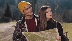 Young smiling happy couple standing in the mountains. They enjoying their hiking. Looking on tourist map. Trying to find. Direction. Slow Motion stock video