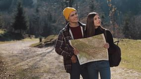Young smiling happy couple standing in the mountains. They enjoying their hiking. Looking on tourist map. Trying to find. Direction. Slow Motion stock video footage