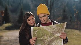 Young smiling happy couple standing in the mountains. They enjoying their hiking. Looking on tourist map. Trying to find stock video footage