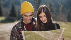 Young smiling happy couple standing in the mountains. They enjoying their hiking. Looking on tourist map. Trying to find. Direction. Slow Motion stock footage