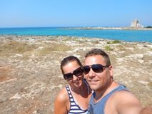 A young smiling happy couple taking a selfie by the sea on a vacation in southern Italy Royalty Free Stock Photos
