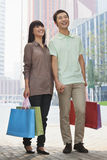 Young, smiling, happy couple walking outdoors in Beijing with colorful shopping bags in hands Stock Photos
