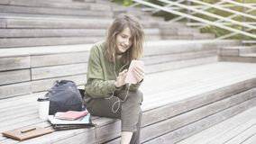 A young smiling happy girl student is texting on the phone outdoors sitting on the stairs. A young smiling happy girl dressed in a green sweat shirt is listening stock photography