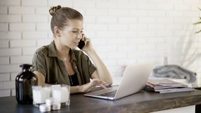 A young smiling happy girl is having a call wotking with a laptop royalty free stock photography