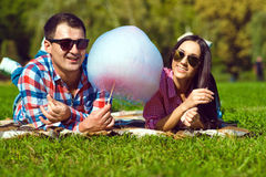 Young smiling happy loving couple in checked shirts and sunglasses lying on the green lawn and eating cotton candy. Outdoor shot royalty free stock photography