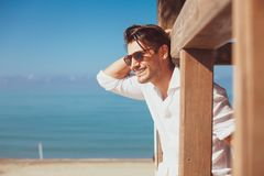 Young smiling happy man on beach vacation. Young smiling happy man on vacation. With sunglasses, overlooking the blue sea. Relaxed on a wooden frame. Intense royalty free stock photo