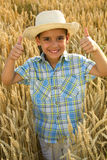 Young smiling healthy boy in fileld of wheat Royalty Free Stock Photos