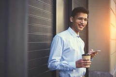 Young smiling hipster guy in good mood enjoying coffee while messaging with friends. In social networks on modern smartphone using free internet connection Royalty Free Stock Photos