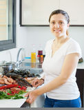 Young smiling housewife with raw seafood Stock Photography