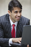 Young smiling Indian businessman using laptop Stock Photo