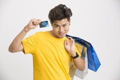 Young smiling Indian man showing his credit card. With shopping bag on white Stock Image