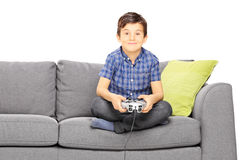 Young smiling kid seated on a sofa playing video game Royalty Free Stock Photos