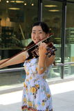 Young smiling lady playing the violin on Broadway,Saratoga Springs,New York,2014 Royalty Free Stock Image