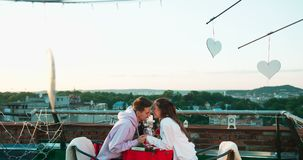 Young smiling loving couple is softly holding hands and rubbing noses during their romantic date on the roof decorated stock video footage
