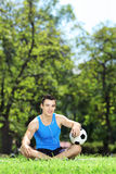 Young smiling male athlete sitting down on a grass with ball in Stock Image
