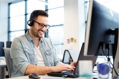 Young smiling male call center operator doing his job with a headset.Portrait of call center worker at office. Young smiling male call center operator doing his Royalty Free Stock Images