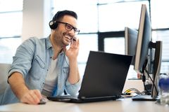 Young smiling male call center operator doing his job with a headset.Portrait of call center worker at office. Young smiling male call center operator doing his Stock Photo