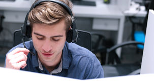 Male call centre operator doing his job. Young smiling male call centre operator doing his job with a headset Stock Photos