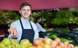 Young smiling male dealer lays out the apples Royalty Free Stock Image