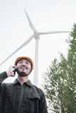 Young smiling male engineer in a hardhat on the phone beside a wind turbine Stock Photography