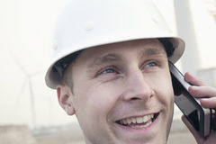 Young smiling male engineer in a hardhat on the phone beside a wind turbine, close-up Royalty Free Stock Photos