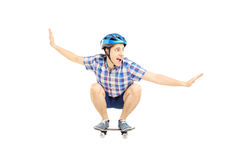 Young smiling male with helmet skating on a skate board. Isolated on white background Stock Photos