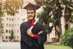 Happy young man on his graduation day. Young smiling male on his graduation day in university holding diploma, copy space. Education, qualification and gown Royalty Free Stock Images