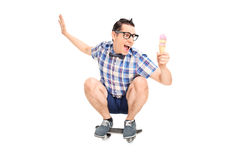 Young smiling male on a skate board with ice cream Stock Photo