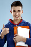 Young smiling male student teenager holding a book. On blue Stock Photography