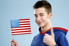 Young smiling male student teenager holding a flag. On blue Stock Photo