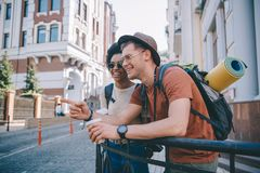 young smiling male tourist with coffee cup pointing by finger to african american girlfriend royalty free stock images