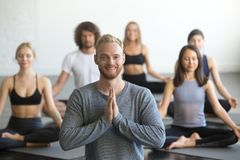Young smiling male yoga instructor and group in lotus pose. Portrait of young friendly smiling male yoga instructor looking at camera, group of sporty people royalty free stock photography