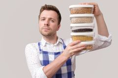 Young smiling man in apron hold several boxes with grains. royalty free stock photo