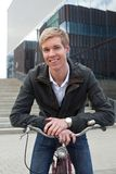 Young smiling man with bicycle. Smiling young handsome blond man standing outdoors with a bicycle royalty free stock image