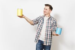 Young smiling man in casual clothes holding empty paint tin cans with copy space isolated on white background. Instruments, accessories, tools for renovation stock photos