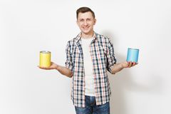 Young smiling man in casual clothes holding empty paint tin cans with copy space isolated on white background. Instruments, accessories, tools for renovation stock photography