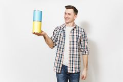 Young smiling man in casual clothes holding empty paint tin cans with copy space isolated on white background. Instruments, accessories, tools for renovation royalty free stock photos