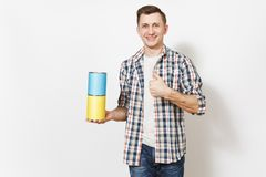 Young smiling man in casual clothes holding empty paint tin cans with copy space and showing thumb up isolated on white. Background. Instruments for renovation royalty free stock image