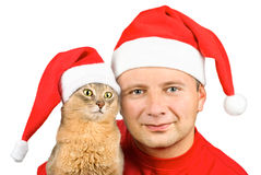 Young smiling man and cat in Santa's hat Royalty Free Stock Photos