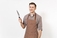 Young smiling man chef or waiter in striped brown apron, shirt holding sharp knife isolated on white background. Male stock photo