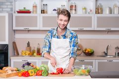 Young smiling man cooking dinner in kitchen Stock Image