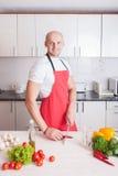 Young smiling man cooking Stock Photos